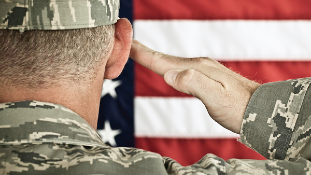 Military soldier saluting American flag
