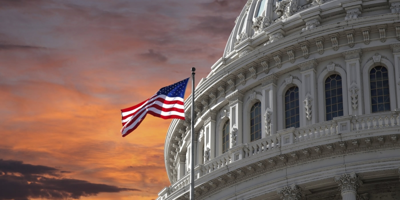 Capitol Dome and U.S. Flag against dramatic sky